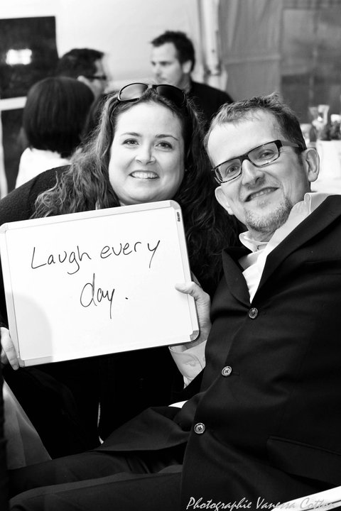 Robert Pearson and his wife holding up a sign that says Laugh every day