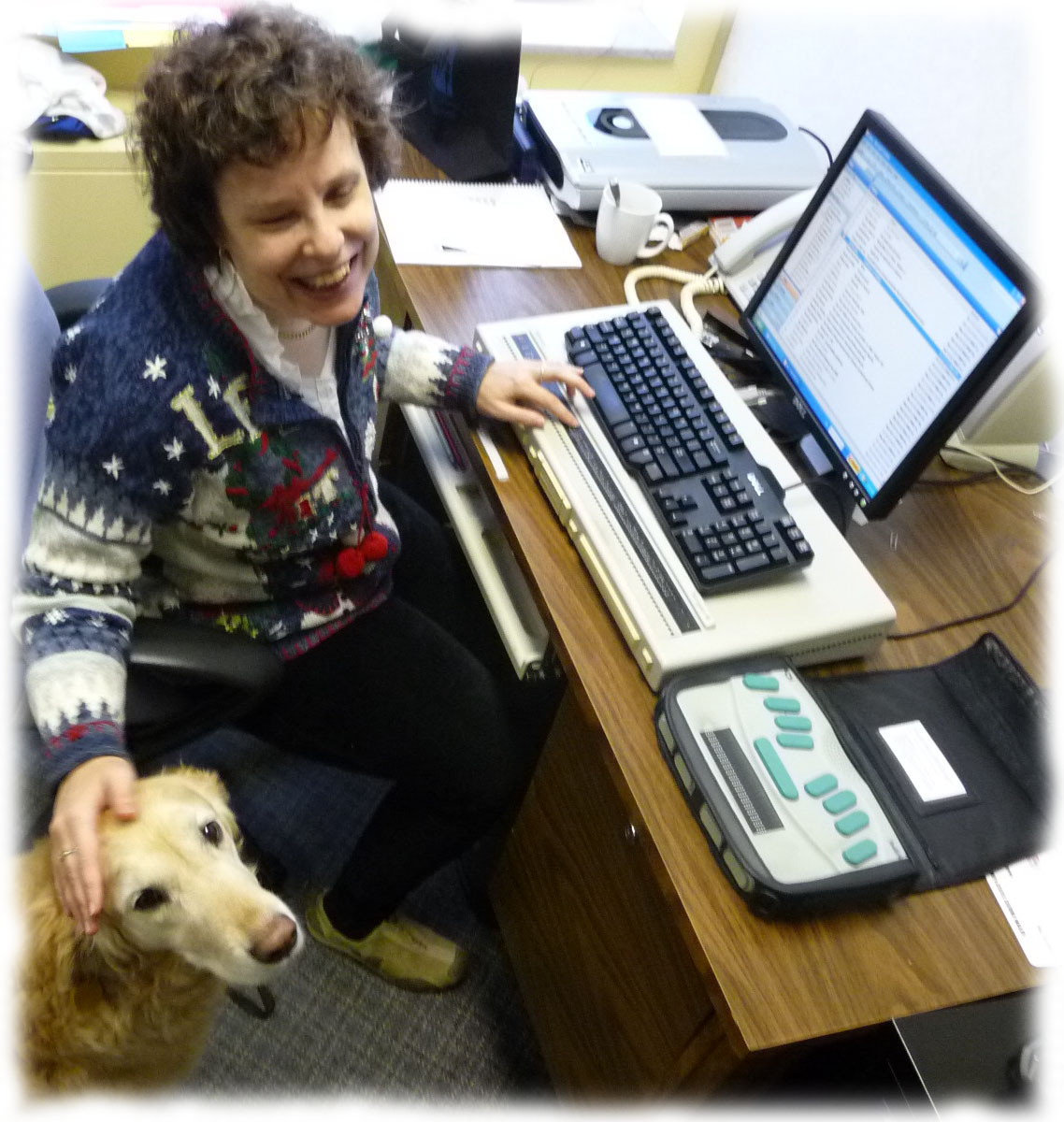 Kim working at her desk with her guide dog